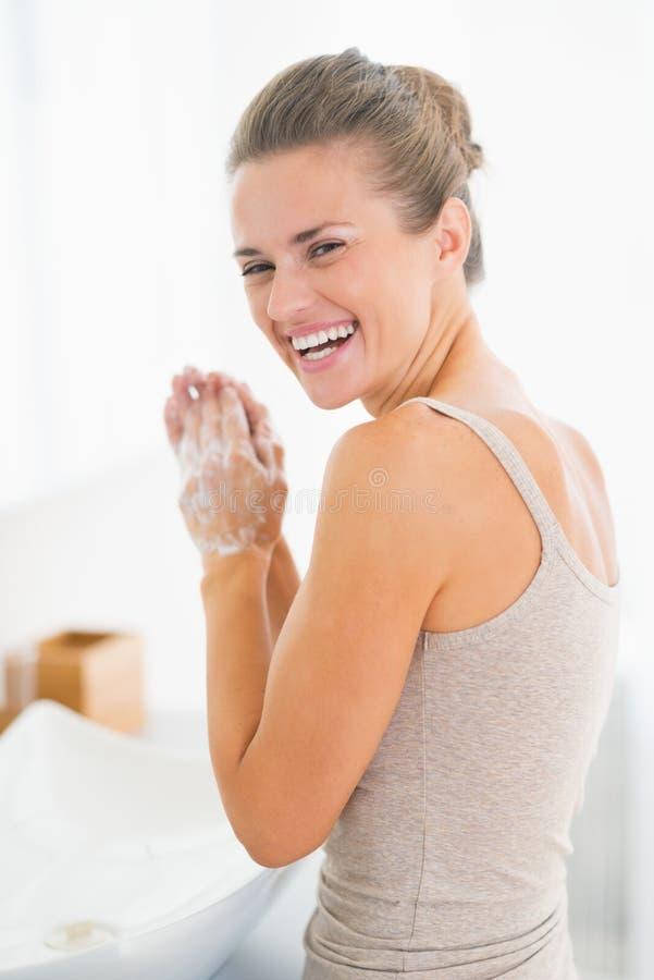 Portrait des mains de lavage de femme heureuse avec du savon photographie stock libre de droits