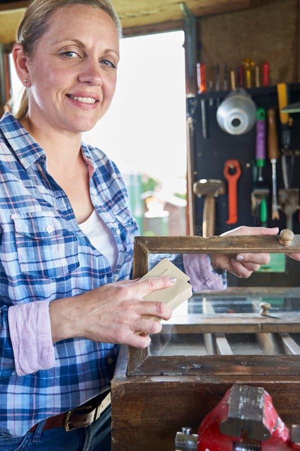 Portrait des meubles mûrs d'Upcycling de femme dans l'atelier à la maison frottant en bas du Cabinet avec le papier sablé image libre de droits