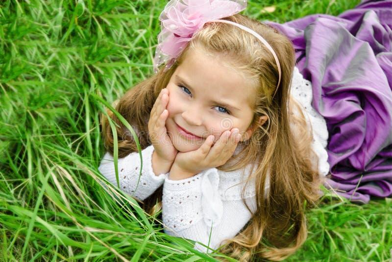 Portrait des netten kleinen Mädchens, das auf einer Wiese liegt lizenzfreie stockbilder