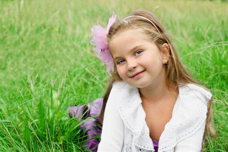 Portrait des netten kleinen Mädchens, das auf einer Wiese liegt stockfotos