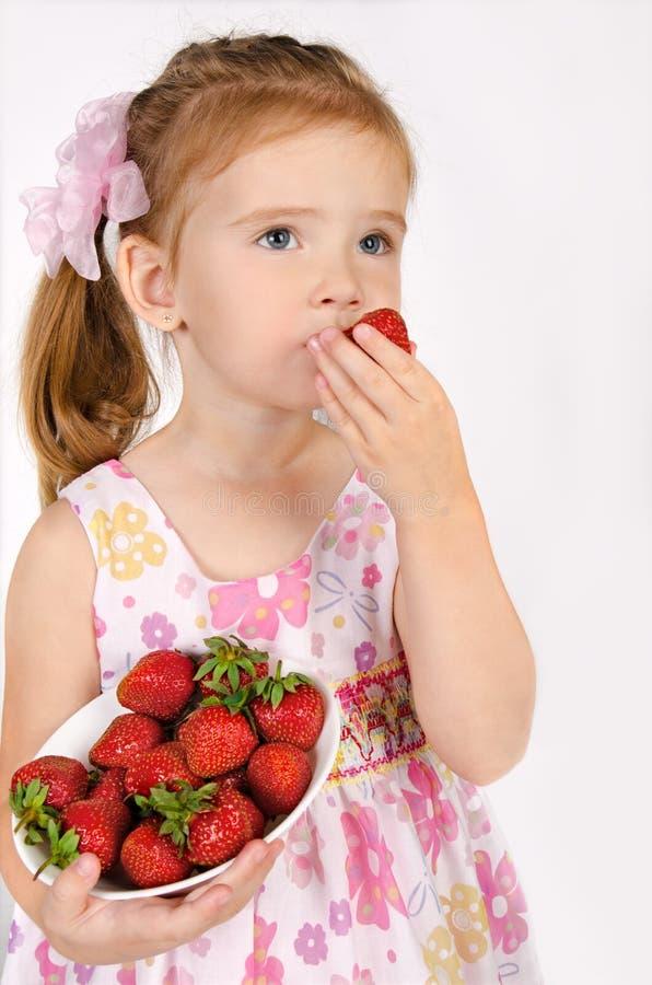 Portrait des netten kleinen Mädchens, das Erdbeere isst stockbild