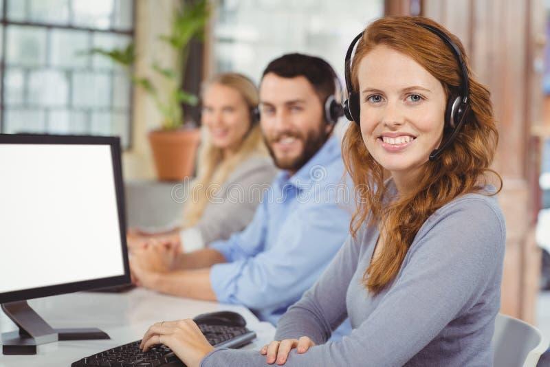 Portrait des opérateurs de sourire travaillant dans le bureau image stock