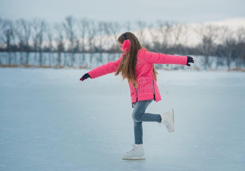 Portrait des patins de petite fille se tenant sur la piste photo libre de droits