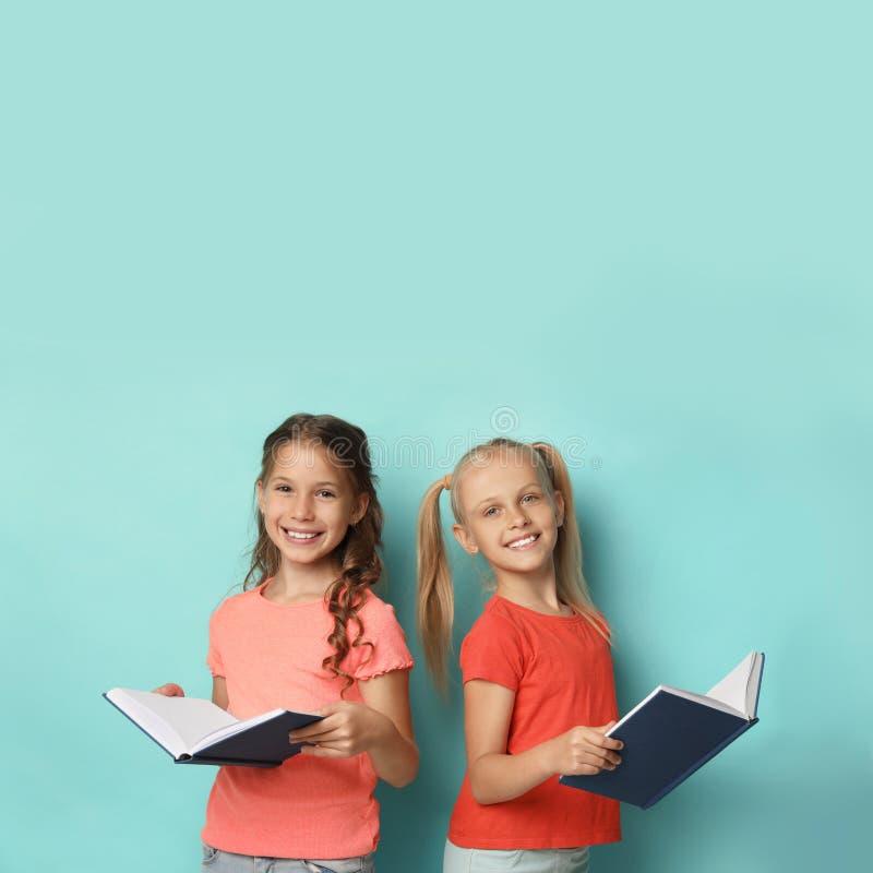 Portrait des petites filles lisant des livres en arrière-plan photo stock