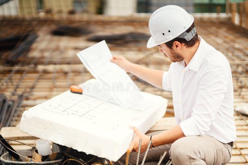 portrait des plans de lecture d'ingénieur sur le chantier de construction image libre de droits