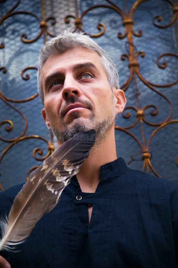 Portrait des plumes d'un homme sexy et d'aigle, et fenêtre médiévale ornementale sur le fond images libres de droits