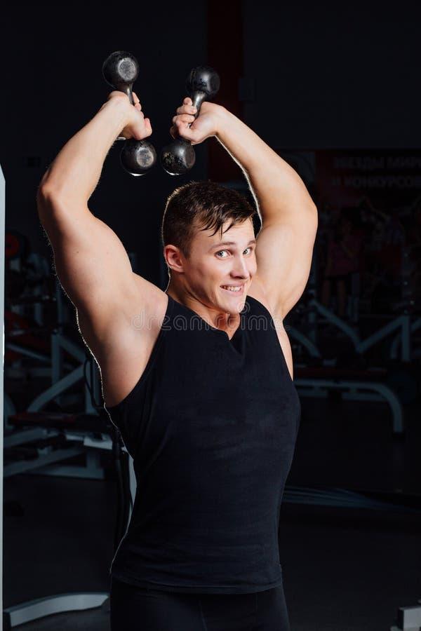 Portrait des poids de levage de sourire d'un jeune homme musculaire sur le fond de gymnase, amical photos stock