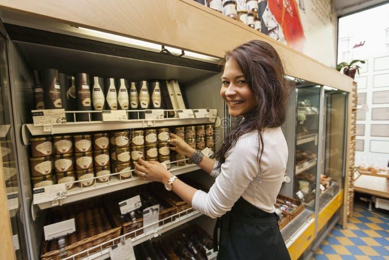 Portrait des produits arranding de sourire de vendeuse dans le supermarché photo libre de droits