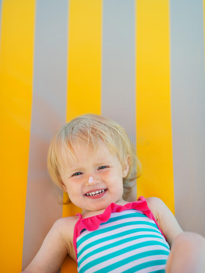 Portrait des Schätzchens mit Sonneblockcreme auf Wekzeugspritze lizenzfreies stockbild