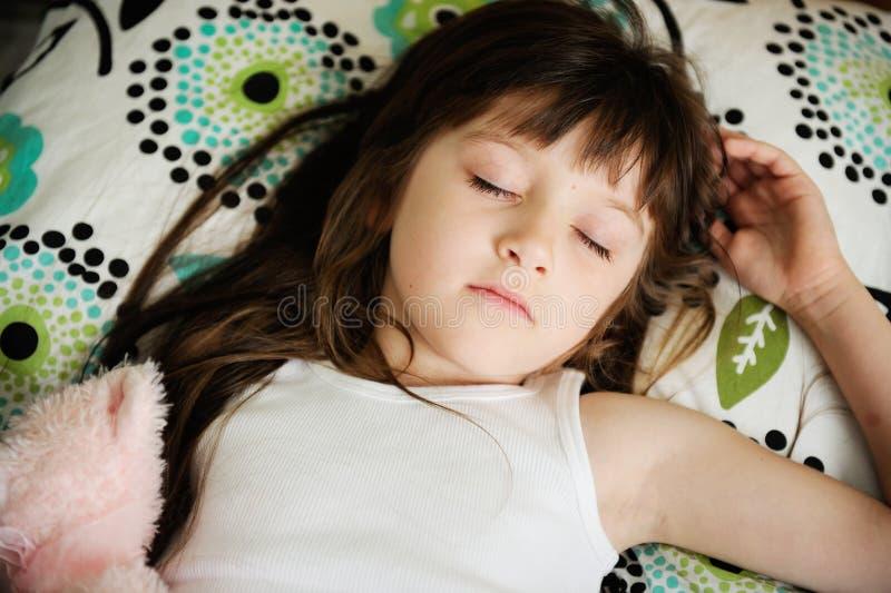Portrait des schlafenden kleinen Mädchens im Bett stockfotos