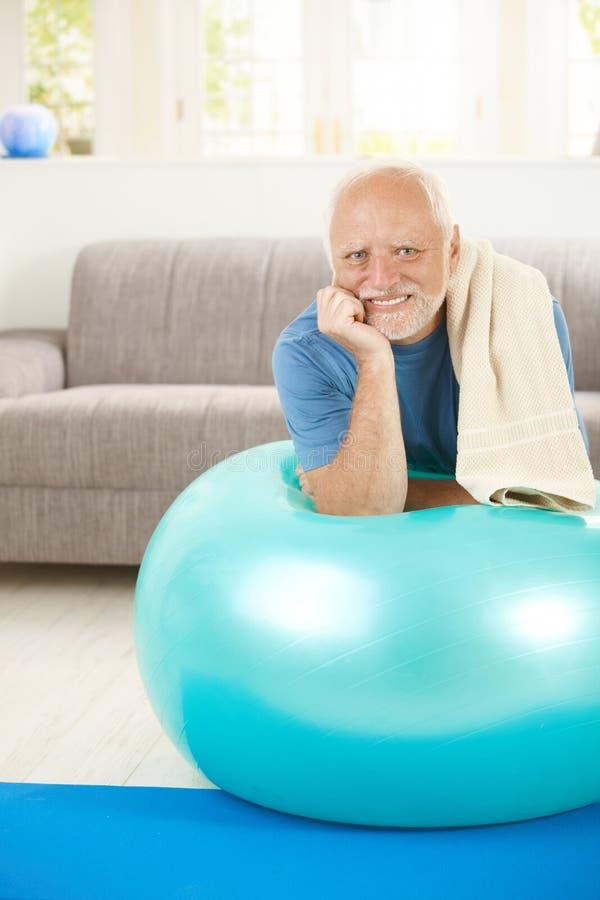 Portrait des sportlichen älteren Mannes mit Übungskugel stockbild
