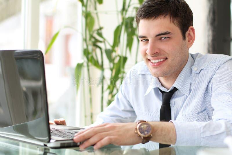 Portrait des stattlichen lächelnden Mannarbeitslaptops lizenzfreies stockfoto