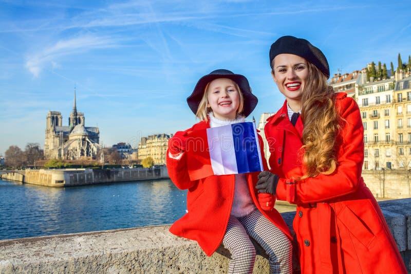 Portrait des touristes de mère et d'enfant à Paris avec le drapeau français photo stock
