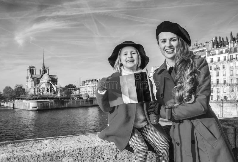 Portrait des touristes de mère et d'enfant à Paris avec le drapeau français photographie stock