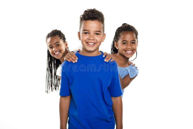 Portrait des trois enfants noirs heureux, fond blanc photos stock
