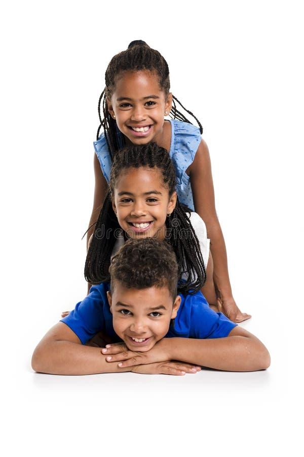 Portrait des trois enfants noirs heureux, fond blanc images stock