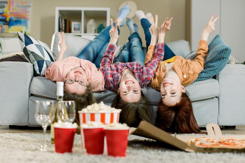 Portrait des trois femmes drôles folles dans le mensonge occasionnel d'équipement à l'envers sur le sofa tenant des mains et rega image stock