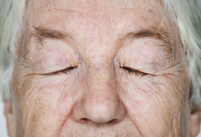 Portrait des yeux d'une femme agée de blanc fermés photographie stock libre de droits