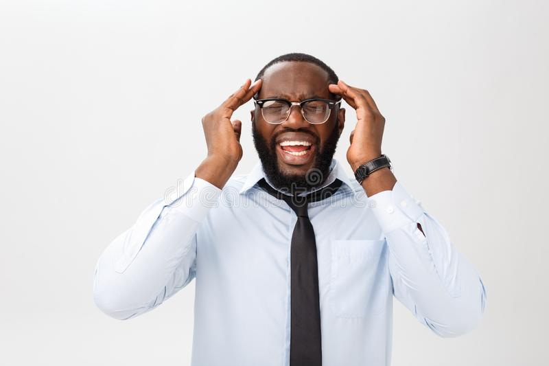 Portrait of desperate annoyed black male screaming in rage and anger tearing his hair out while feeling furious and mad. With something. Negative human face royalty free stock photo