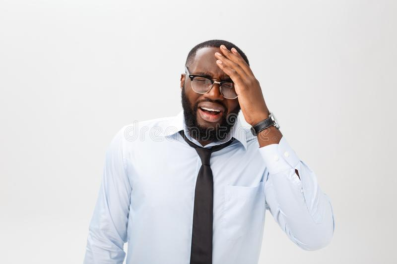 Portrait of desperate annoyed black male screaming in rage and anger tearing his hair out while feeling furious and mad. With something. Negative human face stock photo