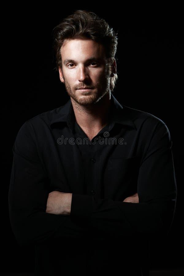 Portrait of determined goodlooking man. Wearing black shirt, black background stock photo