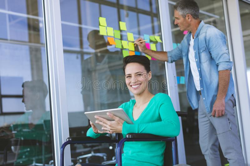 Disabled female executive  smiling while looking at camera while male executive writing on sticky no stock photo