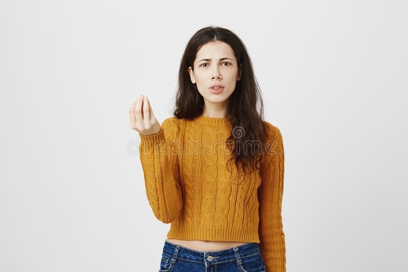 Portrait of disappointed frowning caucasian woman showing italian what do you want gesture, being angry or irritated. Standing over gray background. Girl is royalty free stock images