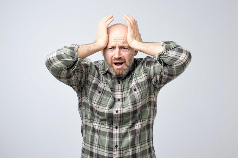 Portrait of disappointed, upset man with stubble cover face with palm, isolated on grey background. royalty free stock photography