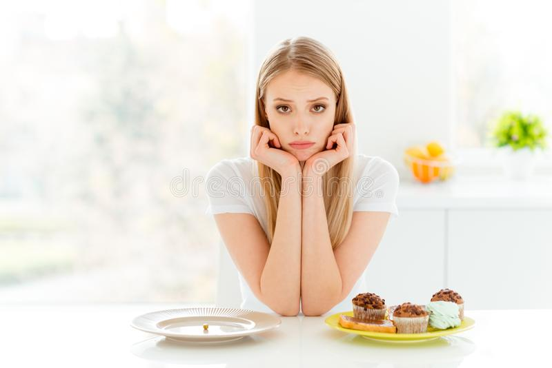 Portrait of disappointed youth hipster decide choose beautiful have problem empty dish hungry bakery confection sit stock images