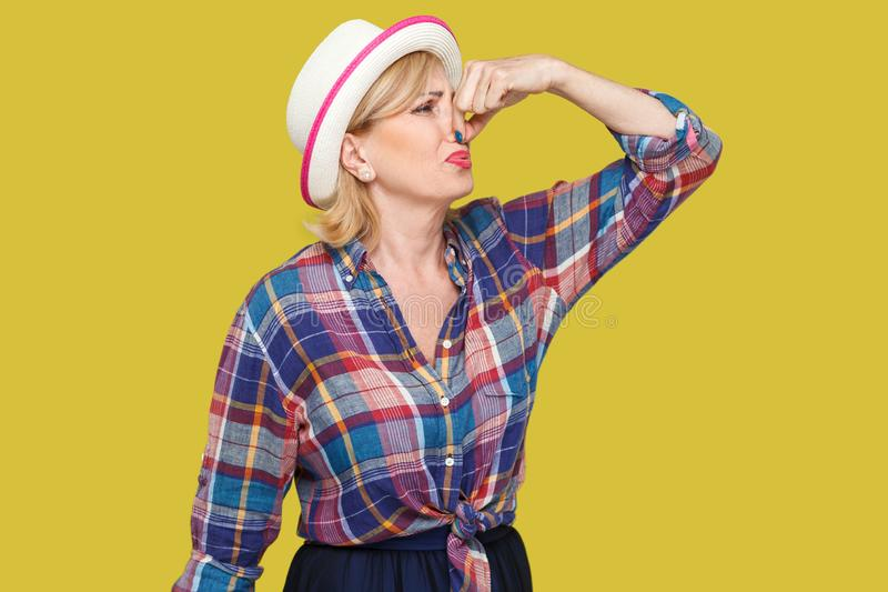 Portrait of disgusted modern stylish mature woman in casual style with white hat standing and pinching her nose because bad smell. Feeling and ignoring. indoor royalty free stock image