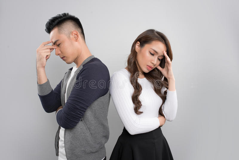 Portrait Of A Displeased Couple Sitting Back To Back On Couch royalty free stock images