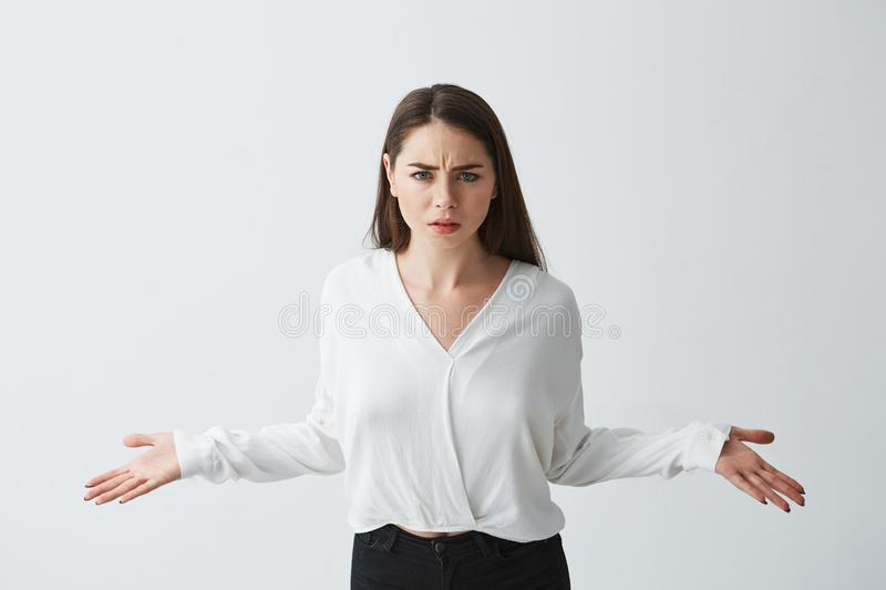 Portrait of displeased young businesswoman spreading hands out looking at camera over white background. royalty free stock images