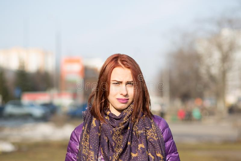 Portrait of a dissatisfied young brown-haired girl in city on a sunny day on bluring background royalty free stock photography