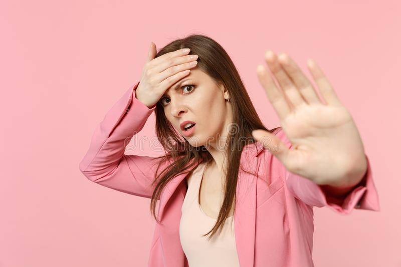 Portrait of dissatisfied young woman in jacket putting hand on head, showing stop gesture with palm isolated on pastel royalty free stock photo