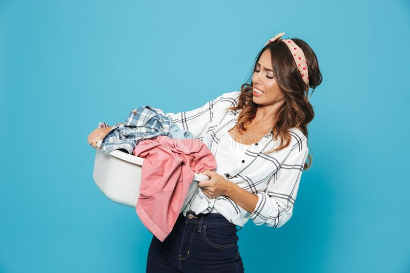 Portrait of dissatisfied young woman 20s carrying laundry basket royalty free stock photos