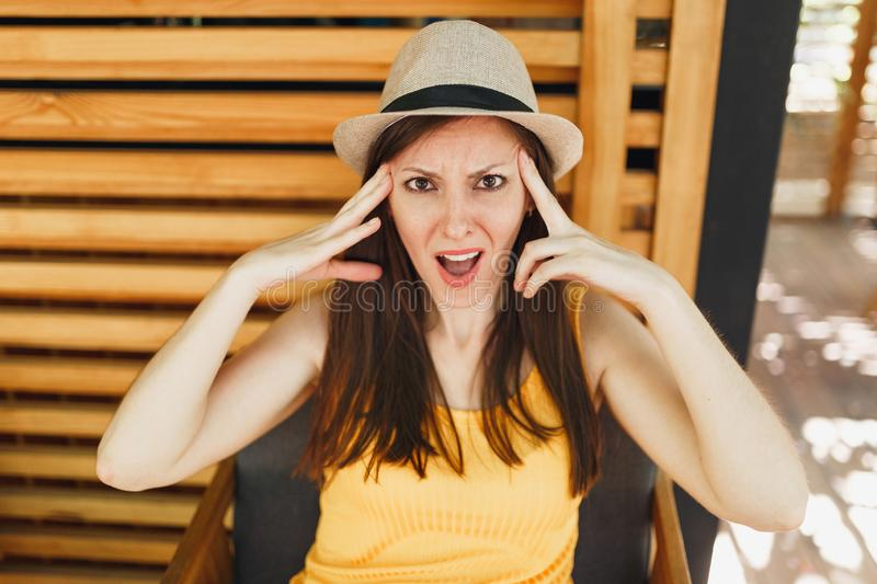 Portrait of dissatisfied young woman in straw summer hat, yellow shirt put hands on head on wooden background in stock image