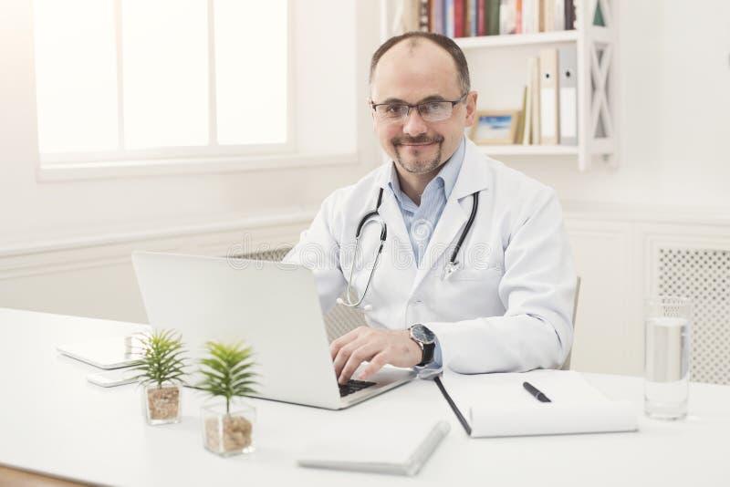 Portrait of doctor in glasses sitting at desktop stock photo