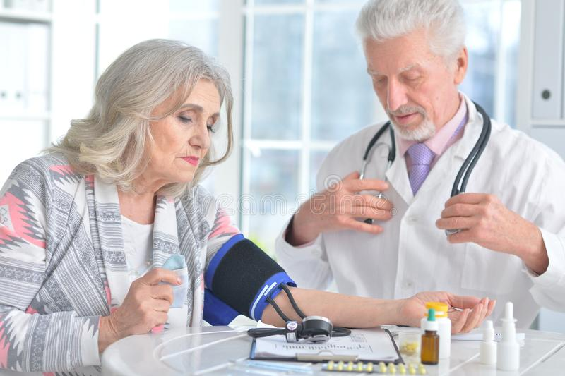 Portrait of doctor measuring blood pressure of woman stock photo