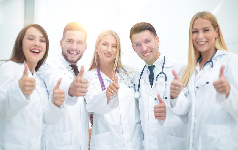 Portrait of a doctor and medical team showing thumb up. Doctor and medical team showing thumb up.the concept of teamwork royalty free stock image