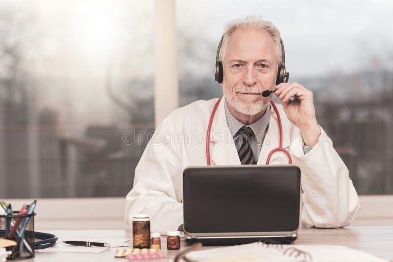 Portrait of doctor during online medical consultation. Portrait of senior doctor during online medical consultation royalty free stock photography