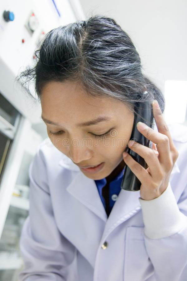 Doctor with phone calls in the laboratory. The portrait of doctor with phone calls in the laboratory royalty free stock photos