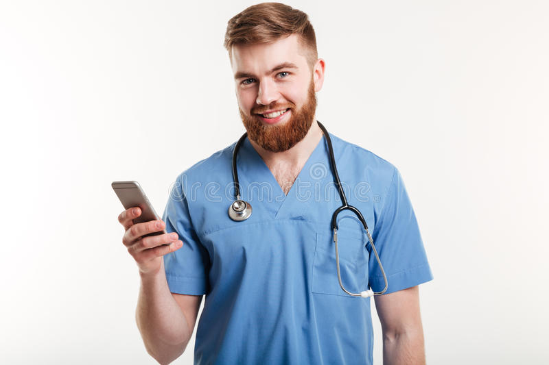 Portrait of doctor with phone. Portrait of male doctor using mobile phone and smiling at camera isolated stock photos