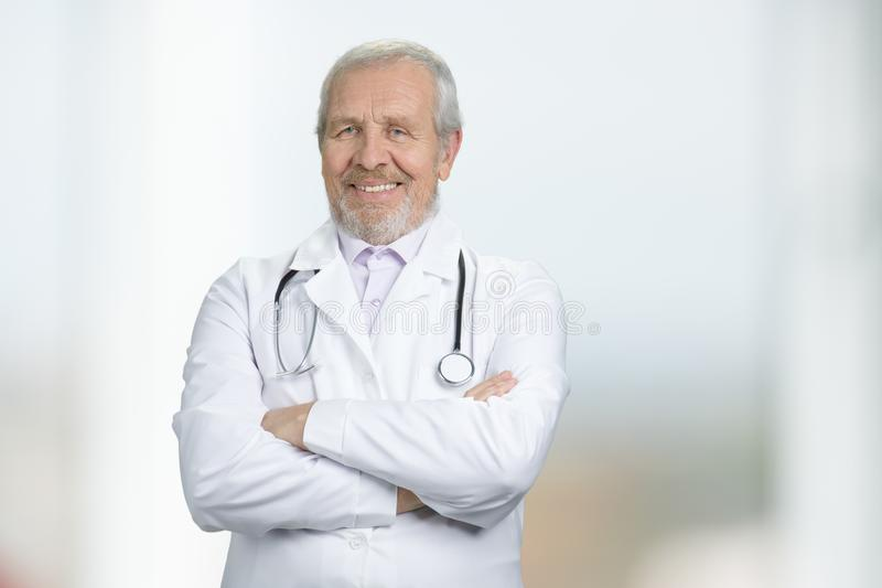 Portrait of doctor standing with arms crossed in hospital. stock photo