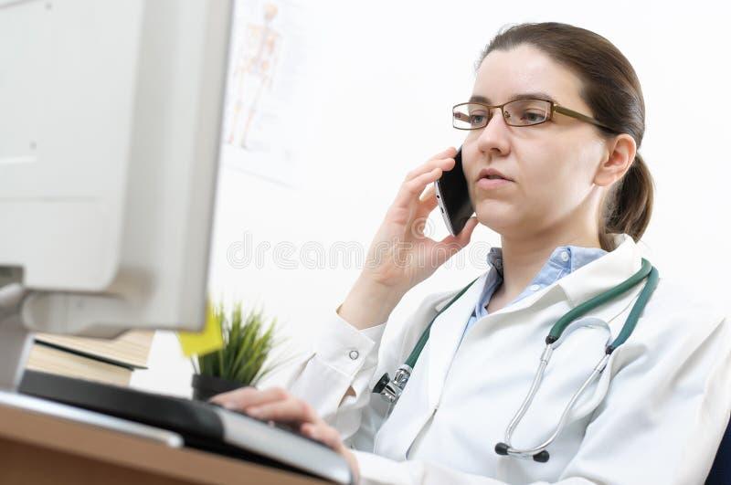 Portrait of a doctor using cellphone. Portrait of a female doctor using cellphone in her office stock photos
