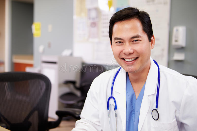 Portrait Of Doctor Working At Nurses Station stock images