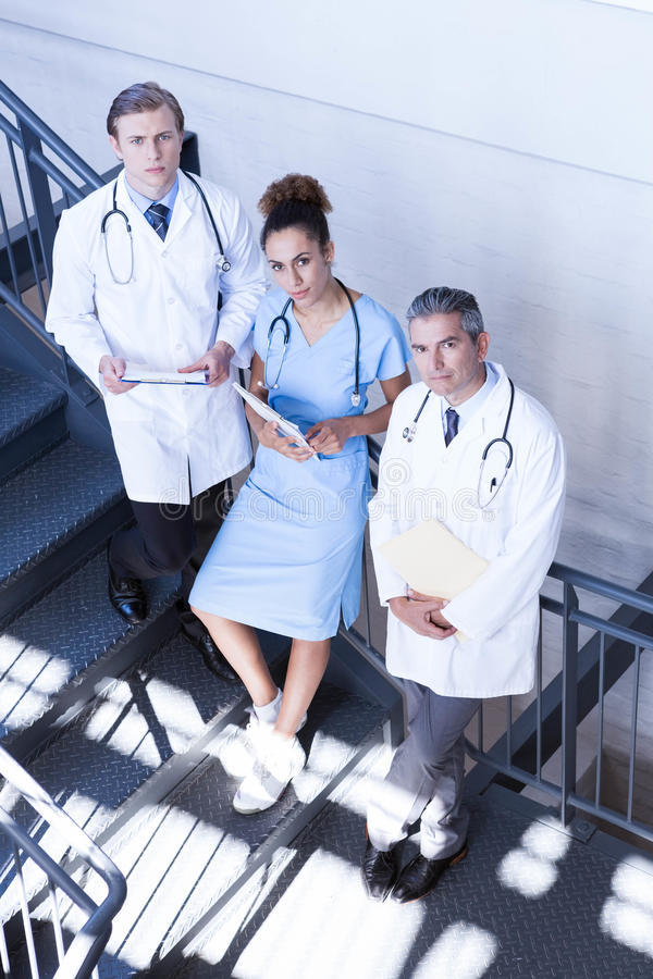 Portrait of doctors standing on staircase with document royalty free stock image