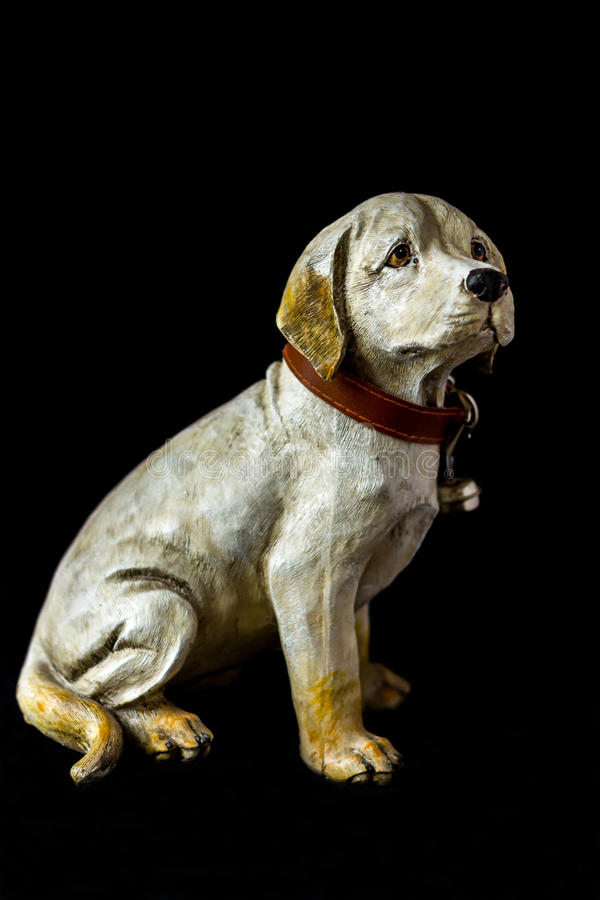 Portrait of a dog sculpture on a black background, whole body. Color stock image