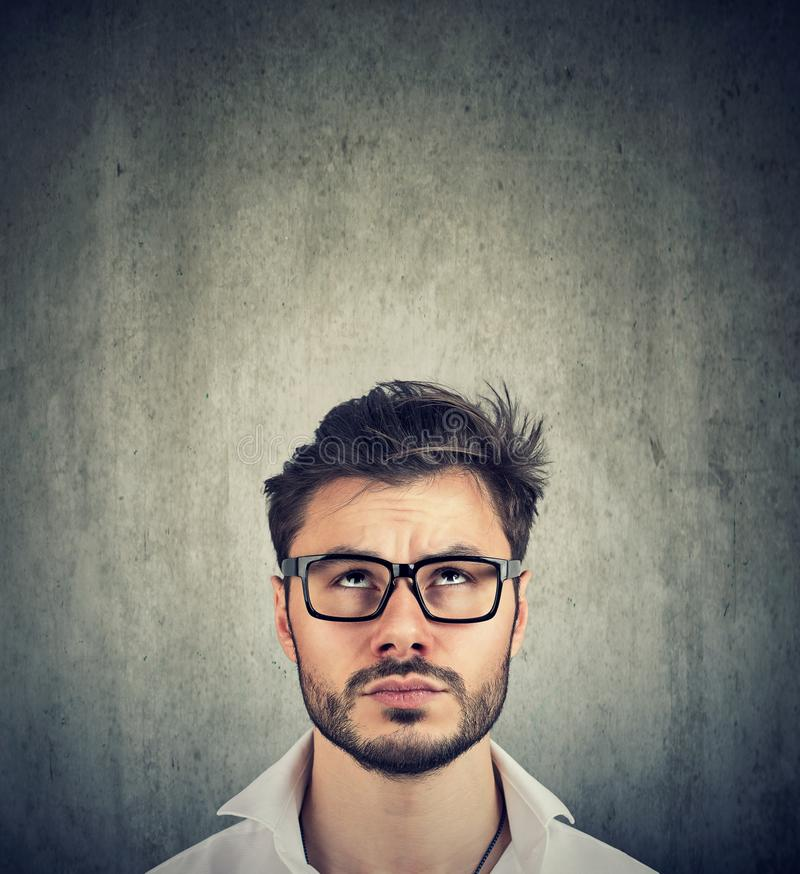 Portrait of a doubtful man with glasses looking up stock image