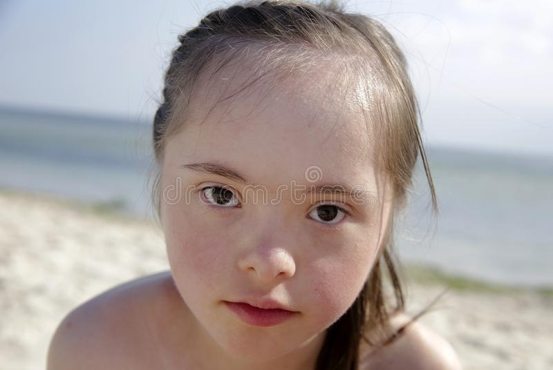 Portrait of down syndrome girl smiling on background of the seaю stock photo