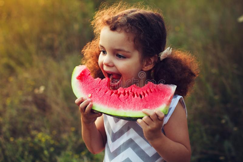 Portrait drôle d'une petite fille aux cheveux bouclés incroyablement belle mangeant la pastèque, casse-croûte sain de fruit, enfa image libre de droits
